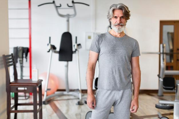 Medium shot man posing at gym