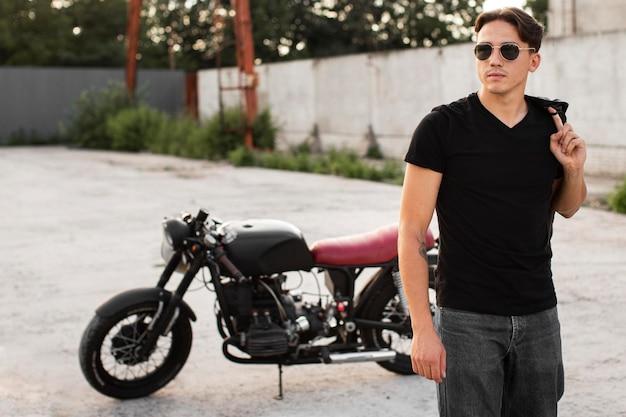 バイクの近くでポーズをとるミディアムショットの男