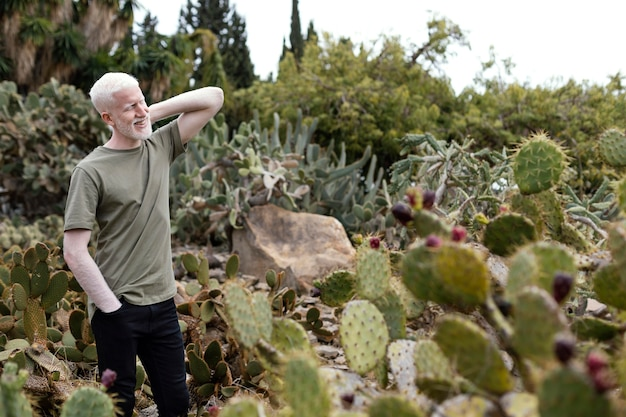 Uomo del colpo medio che posa con il cactus