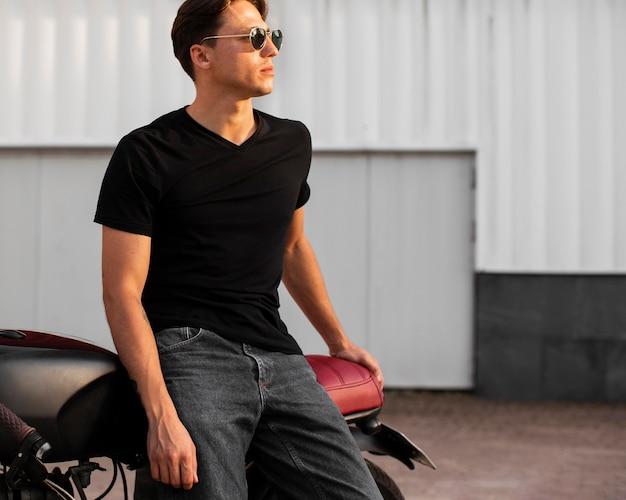 Мужчина среднего кадра позирует с мотоциклом