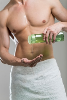 Medium shot man pouring shampoo on hand