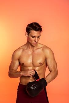 Medium shot man putting on boxing glove