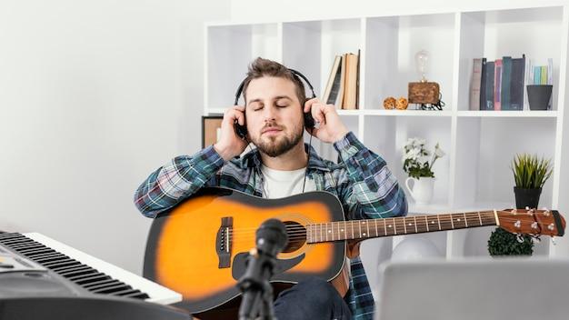 Medium shot man putting on headphones