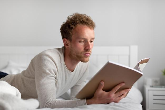 Uomo a tiro medio che legge in camera da letto