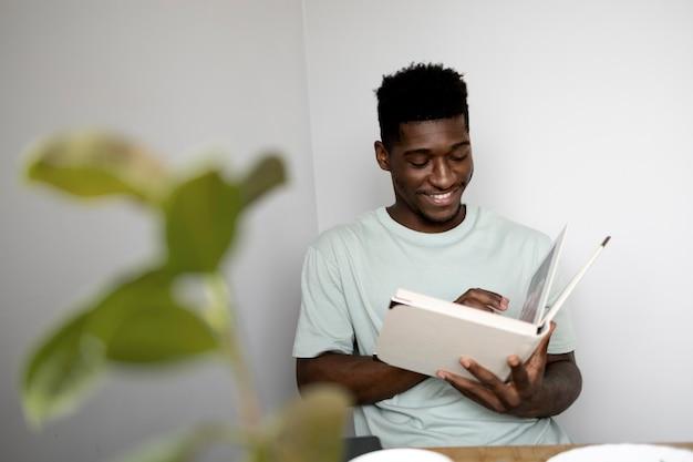 Человек среднего кадра читает книгу