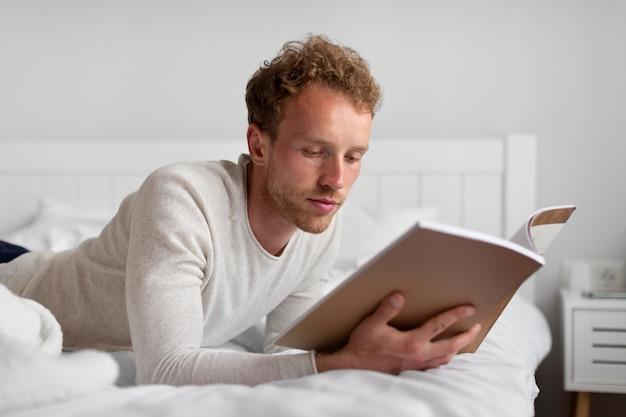 Мужчина среднего кадра читает в постели