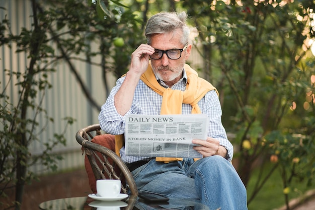 Medium shot man reading newspaper outside