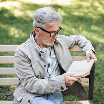 Человек среднего кадра читает на скамейке