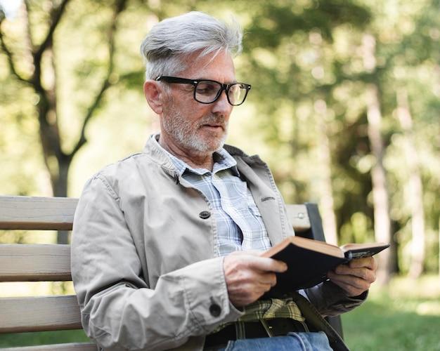 Человек среднего кадра читает на открытом воздухе