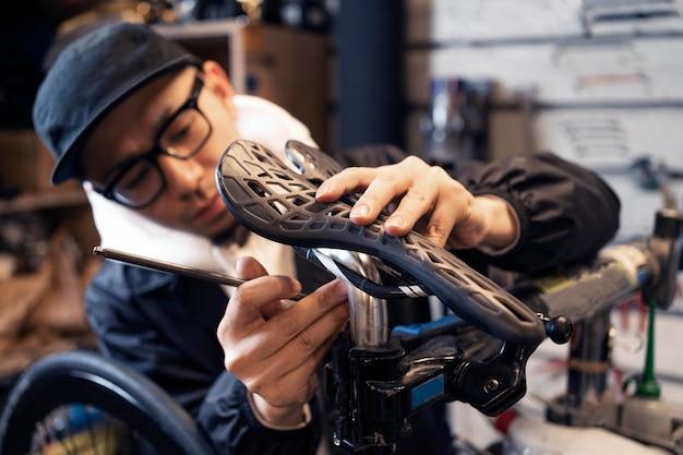 Мужчина среднего кадра ремонтирует велосипед в магазине