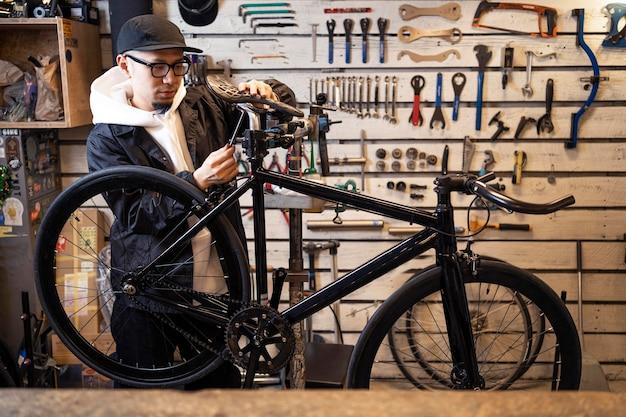 Uomo del colpo medio che ripara bici in negozio