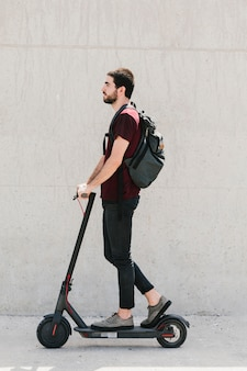 Medium shot man riding e-scooter on street