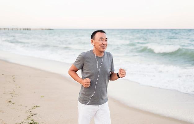 Uomo del colpo medio che corre sulla spiaggia