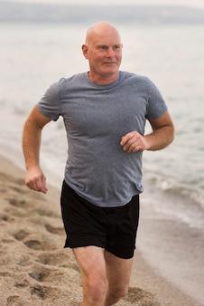 ビーチで走っているミディアムショットの男