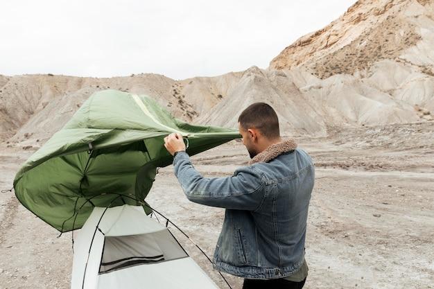 ミディアムショットの男がテントを張る