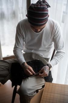 Мужчина среднего кадра шьет в помещении