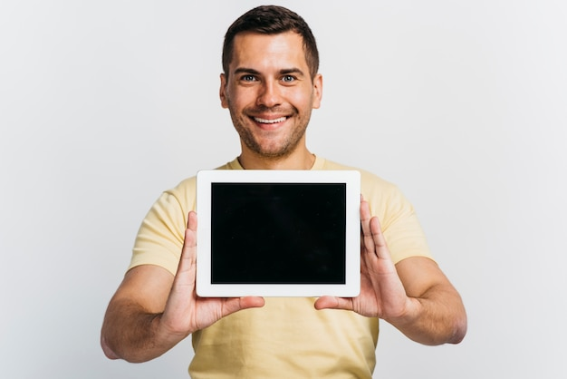 Medium shot man showing a tablet mock-up