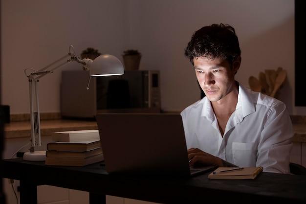 ノートパソコンで机に座っているミディアムショットの男