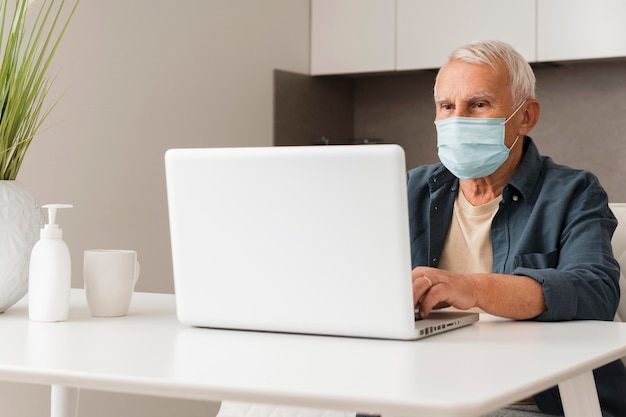 Medium shot man sitting at desk with mask