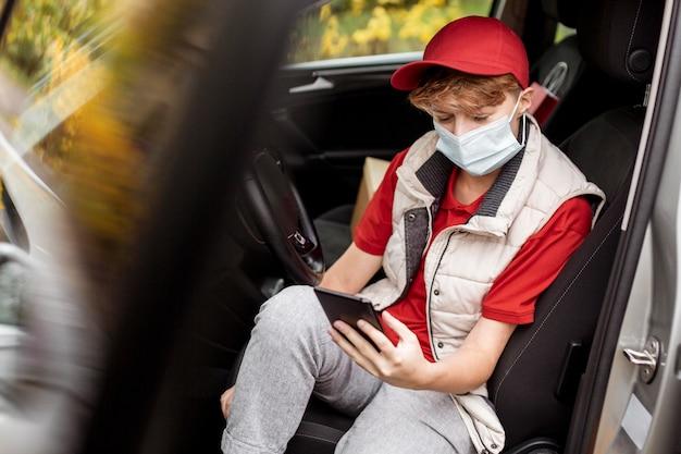 Средний выстрел человек сидит в машине