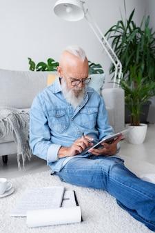 Средний выстрел человека, сидящего на полу с планшетом