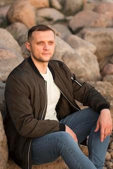 Medium shot man sitting on rocks
