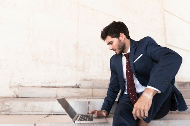 Medium shot man sitting on stairs with laptop