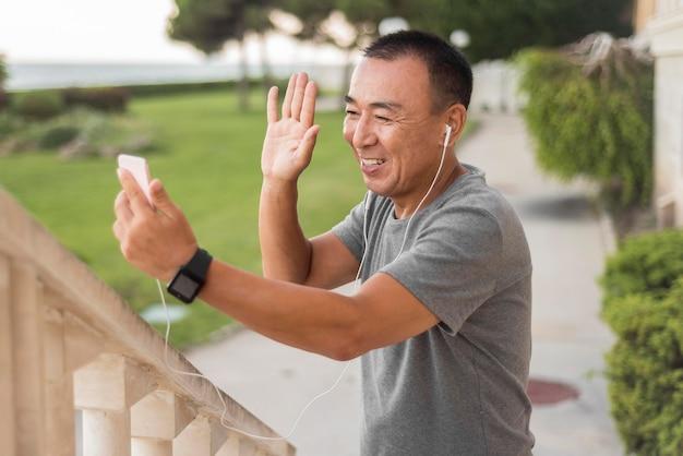 笑顔で手を振っているミディアムショットの男