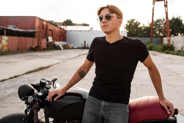 バイクの近くに立っているミディアムショットの男