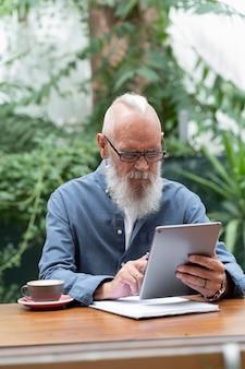 Человек среднего кадра учится с планшетом