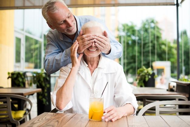 Medium shot man surprising woman at restaurant