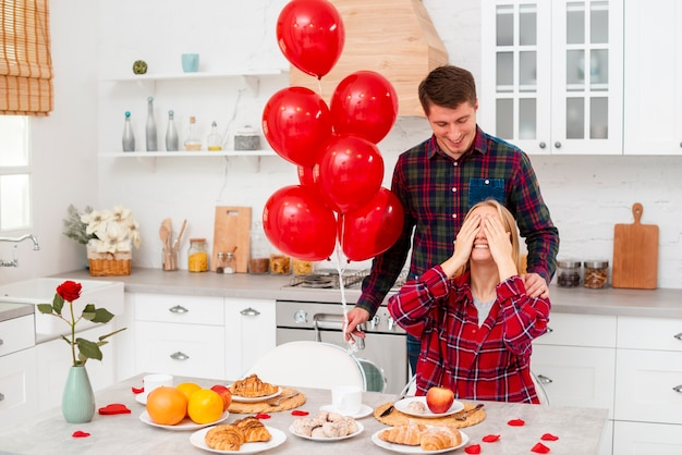 Medium shot man surprising woman with balloons
