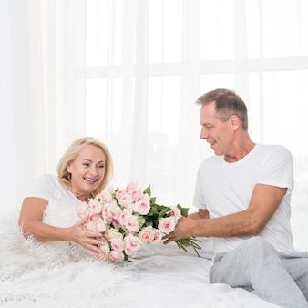 Medium shot man surprising woman with flowers