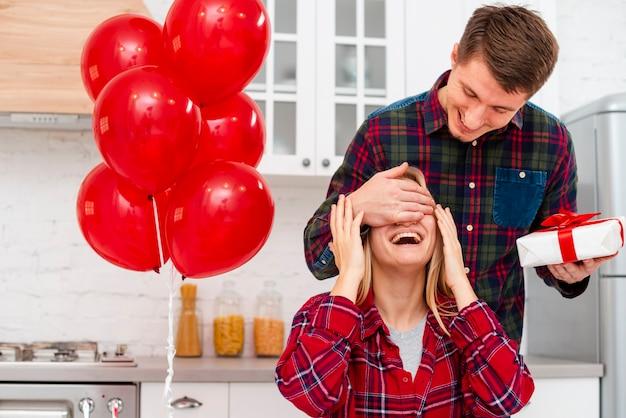 Medium shot man surprising woman with gift