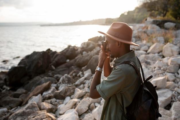 海辺で写真を撮るミディアムショットの男