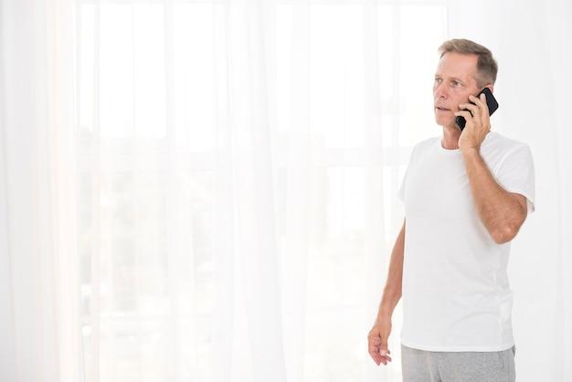 電話で話しているミディアムショットの男