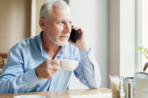 Medium shot man talking on the phone with tea
