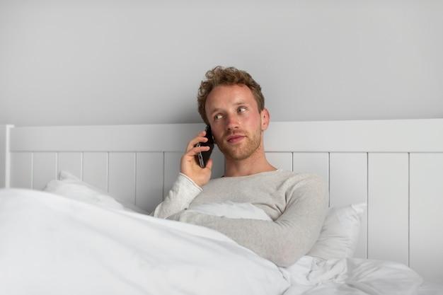 Uomo di tiro medio che parla al telefono