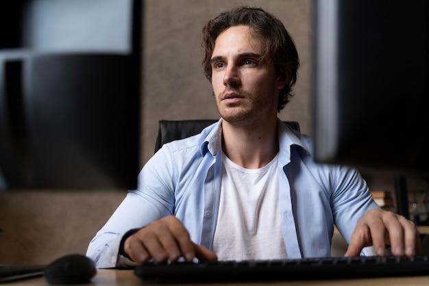 Medium shot man typing on keyboard