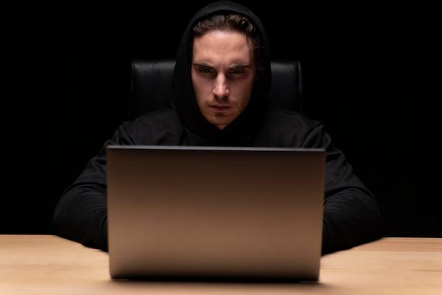 Medium shot man typing on laptop