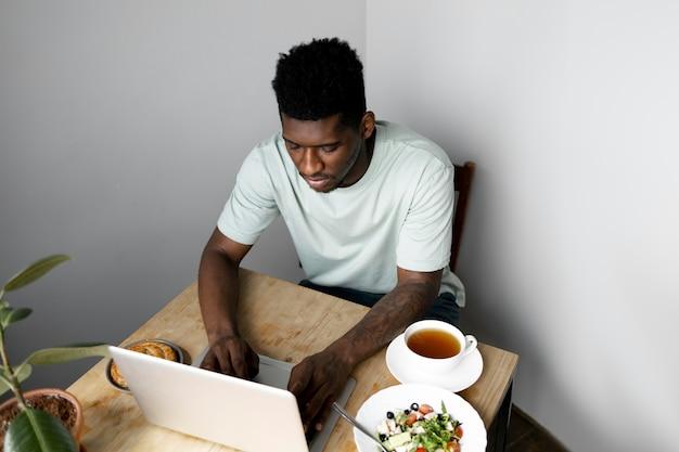 ノートパソコンで入力するミディアムショットの男