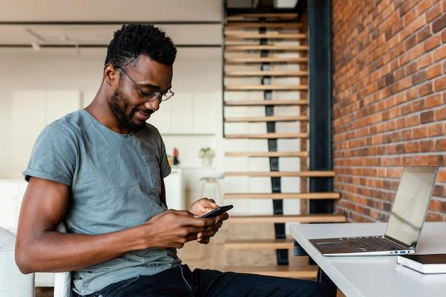 Medium shot man typing on phone