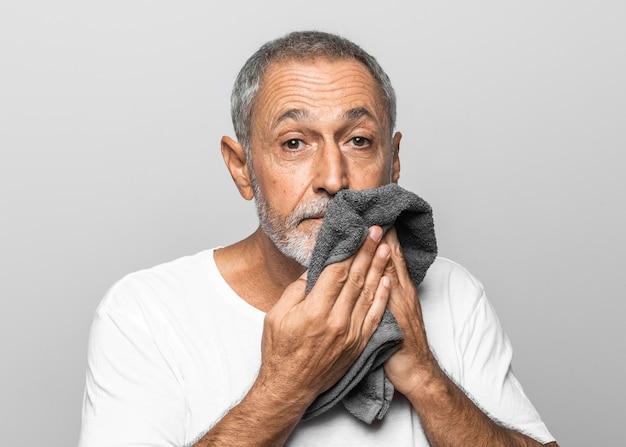 Средний снимок человека, использующего полотенце для лица