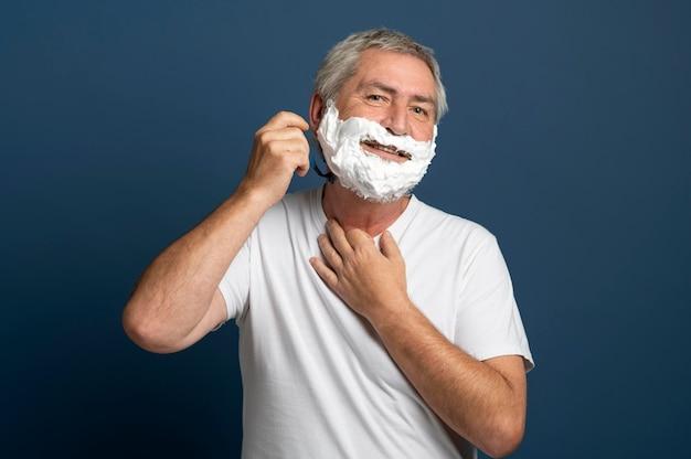 Uomo di tiro medio che usa la crema da barba