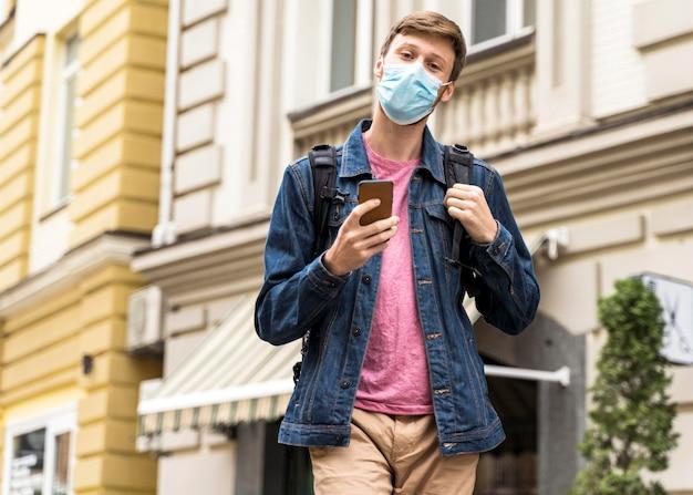 의료 마스크와 함께 밖에 서 걷는 중간 샷 남자