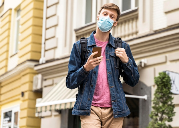 Medium shot man walking outside with a medical mask on