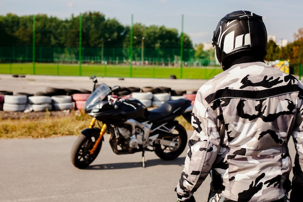 Мужчина среднего роста идет к мотоциклу