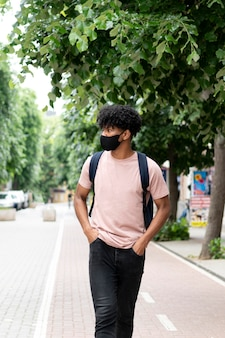 Medium shot man walking with mask