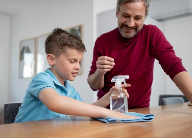 Мужчина среднего кадра смотрит, как ребенок чистит стол