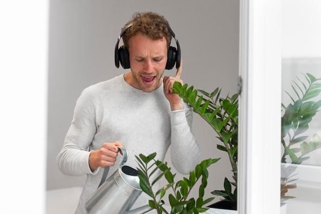 Средний человек поливает растения